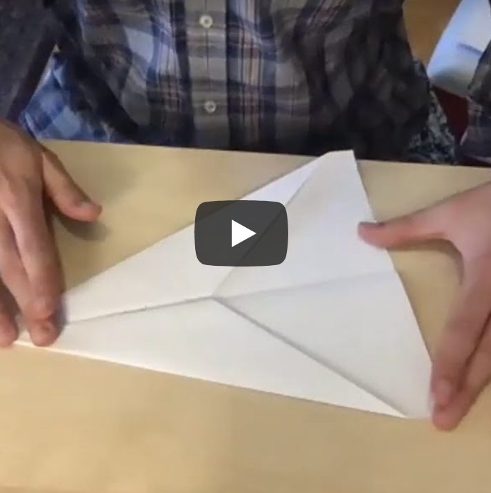 hands folding paper airplane