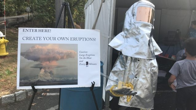 "volcano suit in front of ""create your own eruptions"" sign"